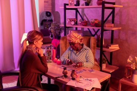 Tarot reading. African american plump fortune-teller wearing a huge ring reading Tarot Imagens