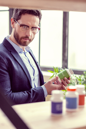 Dealing with stress. Handsome smart businessman holding a bottle with pills while trying to cope with stress