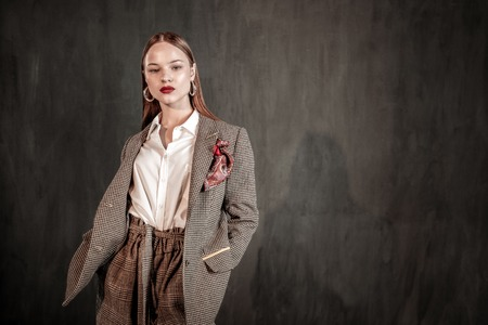 Look at me. Professional fashion model demonstrating stylish coat, standing over grey background Imagens - 118140329