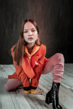 Modern beauty. Serious girl leaning on floor while showing leather shoes Imagens - 118140471