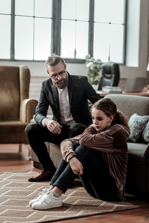 Talking to father. Caring bearded father talking to his depressed daughter sitting on the floor
