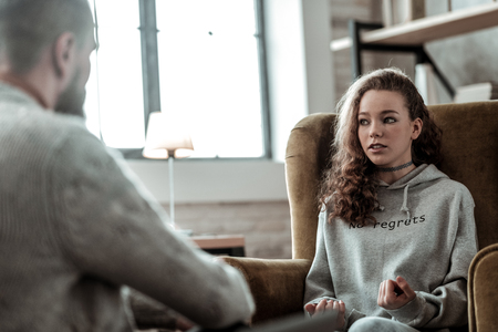 Conversation with psychologist. Appealing teenage girl feeling involved in conversation with psychologist