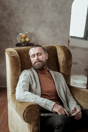 Nap in armchair. Professional counselor wearing grey cardigan having nap in armchair while feeling tired