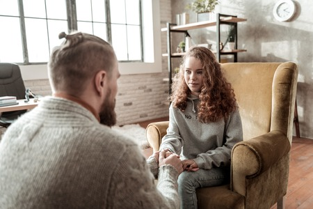 Looking at therapist. Curly appealing teenager wearing grey hoodie looking at her private therapist 免版税图像
