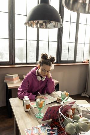 Homework time. Beautiful cute teenage girl wearing pink sweatshirt doing her homework at home