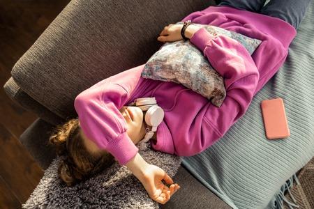 Falling asleep. Top view of girl wearing pink sweatshirt falling asleep at home after school Imagens
