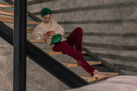 Sitting on stairs. Stylish green-haired woman sitting on stairs in her spacious apartment and using smartphone Stock Photo