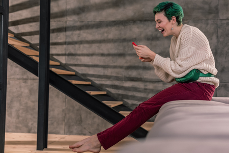 Laughing woman. Laughing woman wearing bright trousers feeling cheerful after seeing funny post
