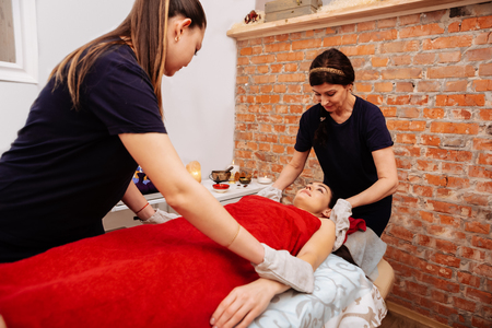 Professional SPA center. Professional workers of SPA salon touching client with scrubbing gloves while she lying on bed