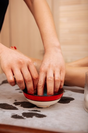Oil on legs. Diligent experienced master taking oil from colored bowl and putting it on bare legs Imagens