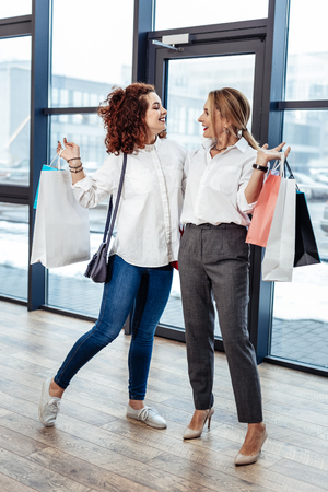 Mother with daughter. Stylish businesswoman wearing high-heeled shoes looking at her older daughter Stock Photo