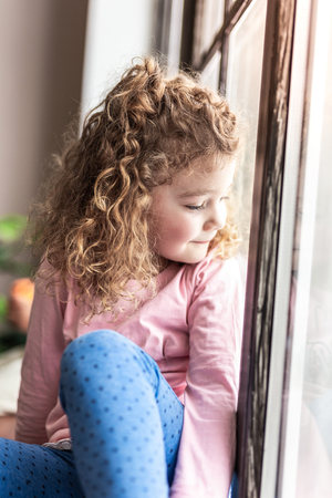 Dreams come true. Beautiful girl expressing positivity while looking through the window