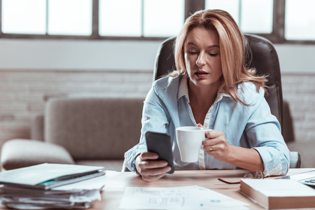 Coffee and phone. Blonde-haired mature businesswoman enjoying break drinking coffee and using smartphone