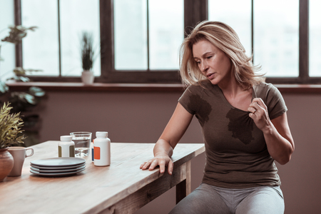 Wet t-shirt. Blonde-haired stressed and depressed woman sweating and having wet t-shirt Standard-Bild