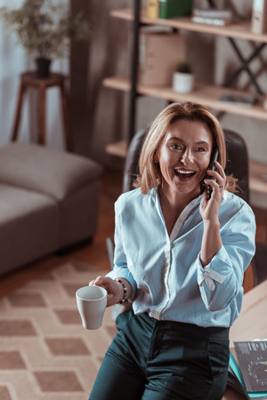 Drinking coffee. Blonde-haired mature woman drinking some coffee and calling her husband Stock Photo - 118196756