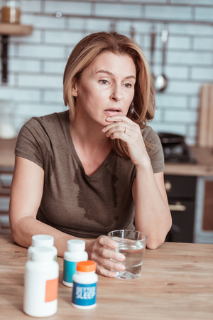 Suicidal thoughts. Blonde-haired stressed woman having suicidal thoughts while looking at medicine Stock Photo