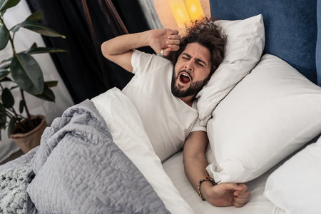 In the morning. Pleasant good looking man yawning while trying to wake up