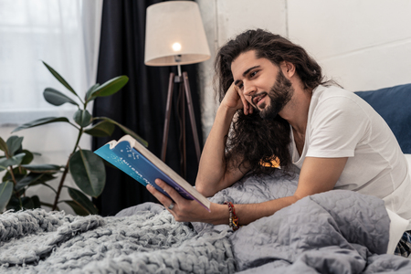 New information. Positive nice man smiling while focusing on reading a book