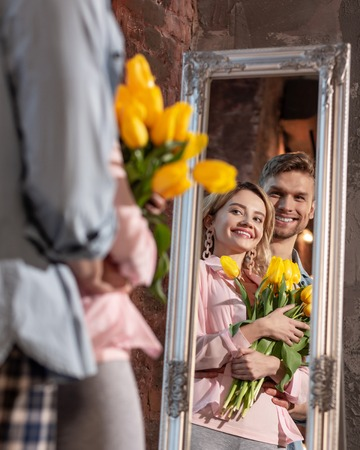 Couple near mirror. Cheerful beaming just married couple smiling broadly while looking into mirror