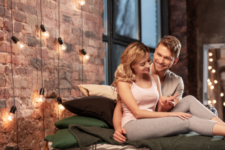 Cozy bedroom. Beaming cheerful couple feeling relieved while spending evening in their cozy bedroom