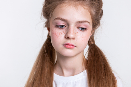 Bunch of freckles. Attractive young girl being sad and dull while looking down with blue eyes