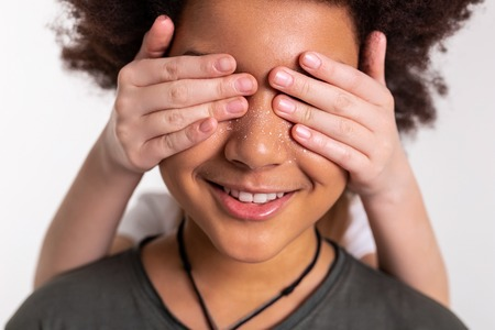 Dark-haired boy. Little girl closing eyes of her dark-skinned smiling friend with curly lush hair Stock Photo