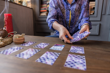 Seeing the destiny. Close up of tarot cards being in female hands while having a fortune telling session Stock Photo