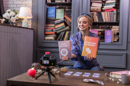 Professional writer. Positive joyful woman holding two books while showing them to the camera Imagens
