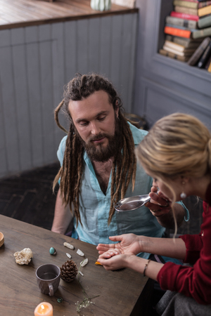 Special potion. Nice bearded man looking at female hands while holding a spoon with a special potion