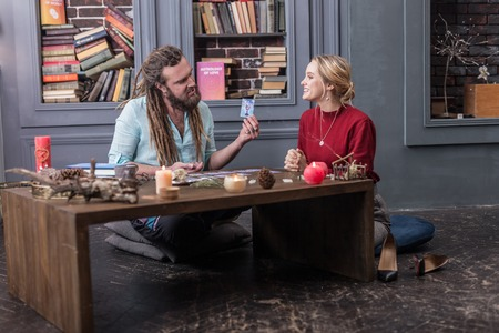 This is your card. Smart bearded man showing a tarot card to a nice young woman while speaking about its meaning Banco de Imagens