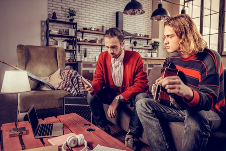 Watching video. Two musicians sitting at the table and watching music video on silver laptop in loft Imagens