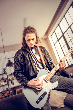 Rock music player. Curly dark-haired rock music player wearing leather jacket composing new song