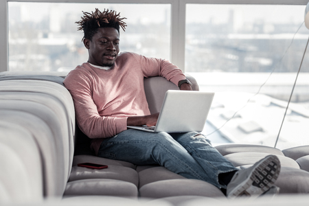 Work on distance. Kind freelancer leaning on sofa and looking at screen of his gadget