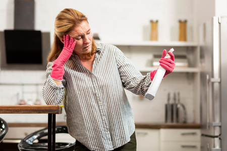 Cleaning chemicals. Blond-haired woman in striped shirt having strong allergy to cleaning chemicals 版權商用圖片