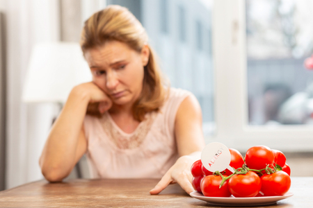 Feeling uncomfortable. Blond-haired woman feeling uncomfortable while having allergy to tomatoes