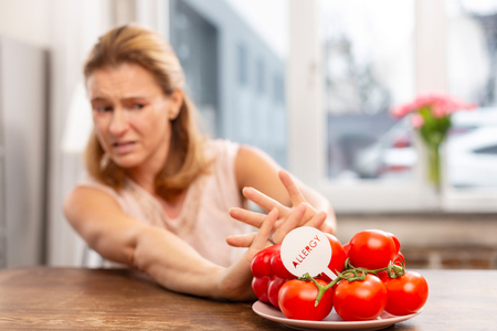 Hypersensitivity to allergens. Blond-haired woman with hypersensitivity to allergens not eating tomatoes