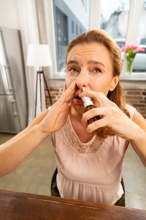 Using nose spray. Dark-eyed mature woman using nose spray while having running nose after allergy Stock Photo