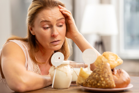 Gluten and dairy. Blond-haired mature woman having strong allergy to gluten and dairy