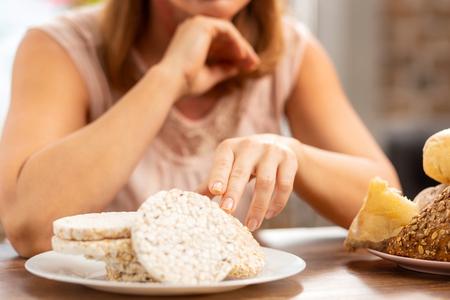 Gluten free crisps. Businesswoman with gluten allergy choosing gluten free crisps for dinner