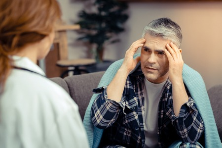 I feel pain. Sad gloomy mature man holding his temples while speaking to the doctor