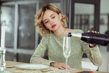 Pouring champagne. Blonde-haired curly woman pouring champagne into glass while feeling stressed 免版税图像