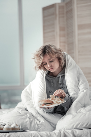 Eating all morning. Stressed and lonely woman sitting in bed and eating all morning after breakup with her man Stock Photo