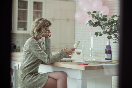 Sitting in kitchen. Elegant woman wearing short shiny dress sitting in the kitchen and drinking champagne 写真素材