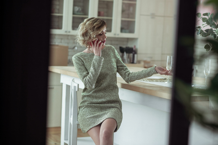 Alone at apartment. Elegant girlfriend calling her man while staying alone at apartment on her birthday Imagens