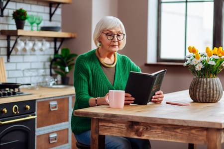 Looking through Bible book. Septuagenarian silver-haired woman wearing stylish glasses and jade green pullover looking through Bible book sitting at kitchen table