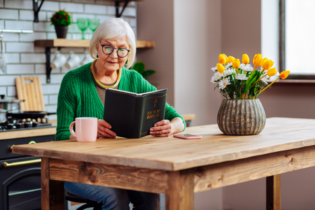 Reading a Bible. Charming dame with short silver hair in glasses wearing emerald sweater carefully reading Bible at kitchen table with flowers on it 免版税图像