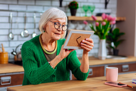 Lovingly palming photo. Aged beautiful silver-haired beaming woman in years and glasses tenderly palming photo frame while sitting at kitchen table Stockfoto