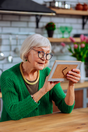 Lovingly look at photo. Aging elegant silver-haired lady in advanced years and glasses lovingly looking at picture in frame sitting at kitchen table