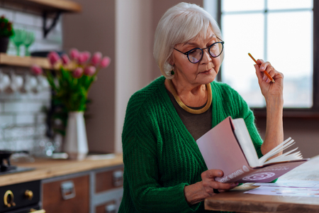 Portrait of woman making notes. Face portrait of focused intellectual stylishly worn aging female being ready to make book notes with pencil