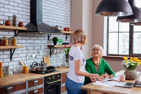 Aged bank borrower. Nice young-adult blond female in volunteer t-shirt kindly explaining appealing smiling elderly dame with short hairdo in glasses main items of overdue loan notification